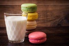 Macarons y vidrio coloridos de leche en fondo de madera oscuro Fotografía de archivo libre de regalías