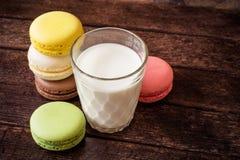 Macarons y vidrio coloridos de leche en fondo de madera oscuro Fotos de archivo libres de regalías
