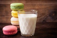 Macarons y vidrio coloridos de leche en fondo de madera oscuro foto de archivo libre de regalías