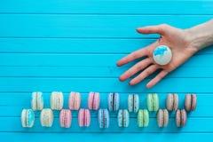 Macaroon или macaron лежат в руке ` s девушки на деревянной предпосылке бирюзы Предложите попробовать печенья миндалины, скопируй стоковые фото