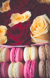 Macaroon and box with flowers roses background Royalty Free Stock Images