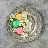 Macaroon cookies flowers. Creative food background. Macaroon cookies with flowers. Antique silver plate. Creative food background Stock Images