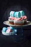 Macaroon cupcakes. Chocolate cupcakes with pink and blue rosewater macaroons on platter Stock Photography