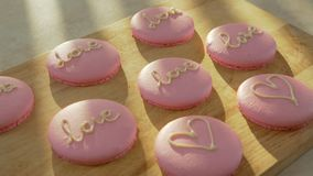 Macaroon decorated with hearts and the words `love` for 14 February. Pink macaroon - biscuits and modern dessert. Macaroon decorated with hearts and the words stock video footage