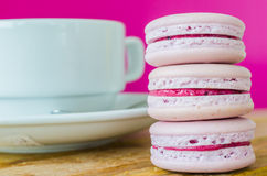 Macaroon. Grape macaroon on the wood table with white tea cup Royalty Free Stock Photo