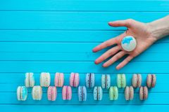 Macaroon or macaron lies in the girl`s hand on a wooden turquoise background. Offer to try almond cookies, copy space.  Stock Photos