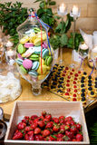 Macaroon, strawberries, cookies and sweets decorated for luxury holiday. Macaroon in a glass vase and other sweets at a party in the French style. The table is stock images