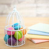 Macaroon. Sweet and colorful macaroon cookies in bird cage with many cute notebook on wooden background with blank space,selective focus, Dessert Stock Photography