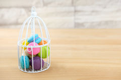 Macaroon. Sweet and colorful macaroon cookies in bird cage on wooden background with blank space,selective focus, Dessert Stock Images