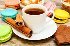 Macaroon with tea, chocolate and cinnamon sticks Royalty Free Stock Photography