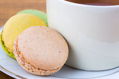 Macaroon and Teacup on wood, Closeup Stock Photo