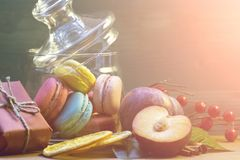 Macaroon, watermelon, plum, orange slices on a wooden table. The concept of home comfort and warmth. royalty free stock images