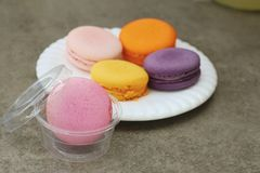 Macaroon in white plates on the background of the cement. Stock Image