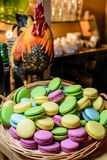 Macaroon in a wicker basket. Multicolored macaroon in a wicker basket on the table with a figure of a rooster royalty free stock image