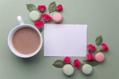Macaroons, καφές και αυξήθηκαν στο πράσινο υπόβαθρο Τοπ όψη Επίπεδος βάλτε στοκ εικόνες