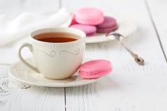 Macaroons με το καυτό τσάι στον ξύλινο πίνακα Στοκ εικόνα με δικαίωμα ελεύθερης χρήσης
