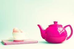 Macaroons σε ένα φλυτζάνι πέρα από το βιβλίο και κόκκινο teapot Στοκ φωτογραφία με δικαίωμα ελεύθερης χρήσης