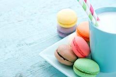Ζωηρόχρωμα macaroons και ένα φλυτζάνι του γάλακτος Στοκ Εικόνες