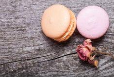2 macaroons и сушат розовый цветок на старой деревянной предпосылке Стоковые Изображения RF