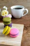 Macaroons и чашка кофе на деревянном столе Стоковое фото RF