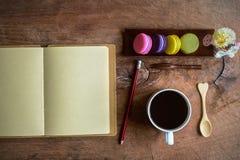 Macaroons и чашка кофе с пустой тетрадью на деревянном столе Стоковая Фотография RF