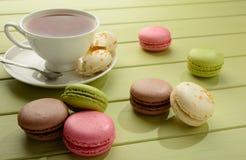 Macaroons и чашка чаю на деревянном столе Стоковые Фотографии RF
