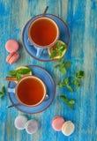 Macaroons и 2 чашки чаю на голубой предпосылке Стоковые Изображения