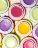 Macaroons формируют сладостные бальзамы губы, яркие цвета, белую косметику предпосылки Стоковая Фотография RF