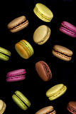 Macaroons. Typical french macaroons biscuits on black background Stock Images