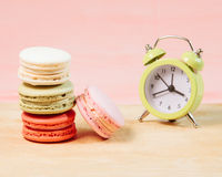 Macaroons and alarm clock on table, vintage stylized photo Stock Photos