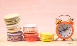 Macaroons and alarm clock on table, vintage stylized photo Stock Images