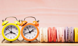 Macaroons and alarm clock on table, vintage stylized photo Royalty Free Stock Images