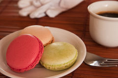 Macaroons as desert. A plate with 3 macarons, coffee and gloves Royalty Free Stock Photography
