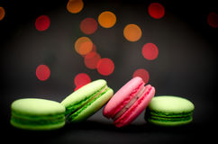 Macaroons with background lights. Green and pink macaroons with blurred lights in the background Stock Photography