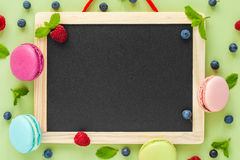 Macaroons, berries, mint leaves and empty black menu board. stock images