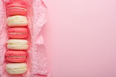 Macaroons in a box on a light pink background, flatlays, with an empty space for writing on a postcard or congratulations.  stock photos