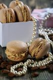 Macaroons in the box, pearls and coffee beans. Royalty Free Stock Images