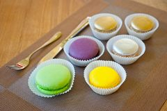 Macaroons of bright different colors in paper forms close-up shot next to cutlery royalty free stock image