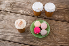 Macaroons with coffee on wooden table Royalty Free Stock Photo