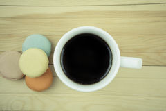 Macaroons with coffee on wooden Royalty Free Stock Image
