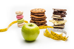 Macaroons, cookies, chocolate bars, apple and measuring tape Royalty Free Stock Image