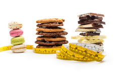 Macaroons, cookies, chocolate bars and measuring tape Royalty Free Stock Photo