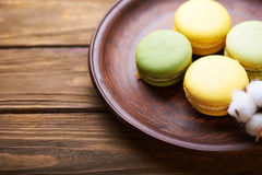 Macaroons and cotton flowers on wooden table Stock Image