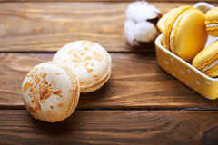 Macaroons and cotton flowers on wooden table Royalty Free Stock Photography