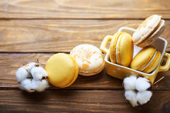 Macaroons and cotton flowers on wooden table Royalty Free Stock Image