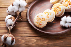 Macaroons and cotton flowers on wooden table Stock Photos