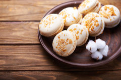Macaroons and cotton flowers on wooden table Stock Photography