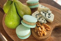 Macaroons, Crushed Walnuts And pears On A Wooden Surface stock image