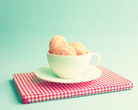 Macaroons in a cup over book Stock Photo