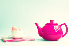 Macaroons in a cup over book and red teapot Royalty Free Stock Photo